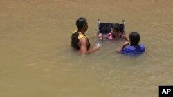 Una familia venezolana, uno de ellos en silla de ruedas, se baña en el río Branco, en Boa Vista, estado de Roraima, Brasil, Marzo 11, 2018.