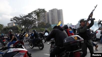 "Soldiers and people react to the sound of gunfire near the Generalisimo Francisco de Miranda Airbase ""La Carlota"" in Caracas, Venezuela, April 30, 2019."