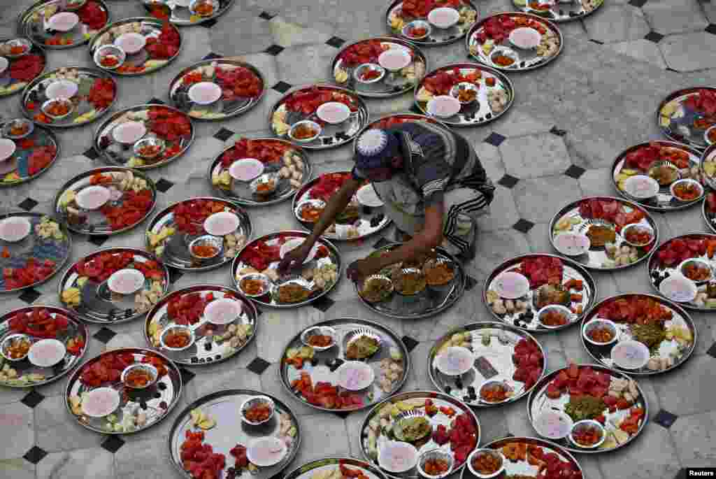 A Muslim man prepares food for an Iftar (breaking of fast) meal inside a mosque during the holy month of Ramadan in Ahmedabad, India.