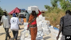 A displaced woman walks with a box of food on her head from a food distribution center at a U.N. compound in Juba, Dec. 23, 2013. (WFP)