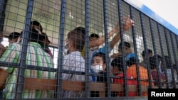 Suspected Uighurs are transported back to a detention facility in the town of Songkhla in southern Thailand after visiting women and children at a separate shelter, March 26, 2014.