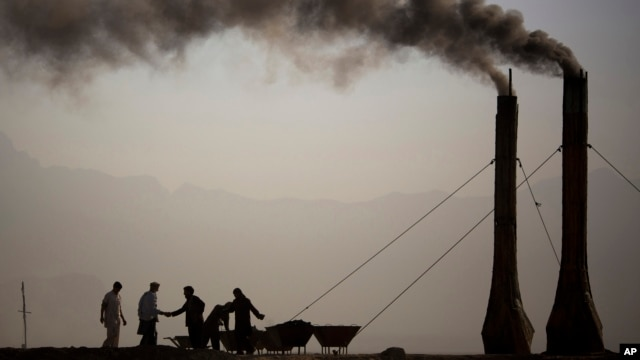 At a brick kiln, workers greet each other while preparing the kilns to fire bricks early morning on the main highway leading to Bagram, on the outskirts of Kabul, Afghanistan, Saturday, Oct. 26, 2013.