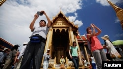 Tourists take pictures as they visit the Grand Palace in Bangkok.