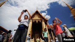 Tourists take pictures as they visit the Grand Palace in Bangkok