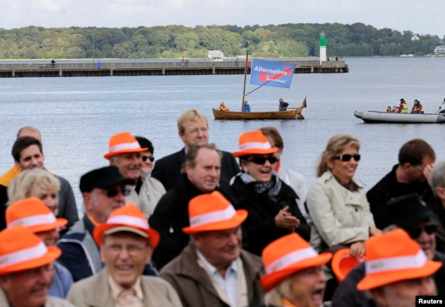 Supporters of the anti-euro party, the Alternative for Germany (AfD) sail a boat next to the square where German Chancellor Angela Merkel is holding an election campaign rally in Stralsund, Sept.21, 2013.