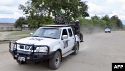 FILE - Congolese troops and UN soldiers are seen atop a truck in the town of Kiwanja.