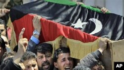 Mourners carry a coffin draped in the opposition flag at a funeral for some of those killed by Thursday's airstrike on rebel forces in Benghazi,Apr 8 2011