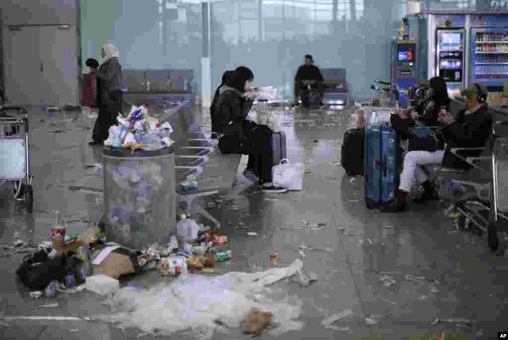 Passengers sit surrounded by rubbish and papers thrown by cleaning workers as they hold the fourth day of a strike at Barcelona airport in Prat Llobregat, Spain.