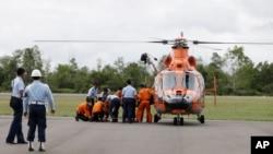 印尼搜救机构官员和空军军人从直升机抬下亚航失事客机遇难者的遗体。