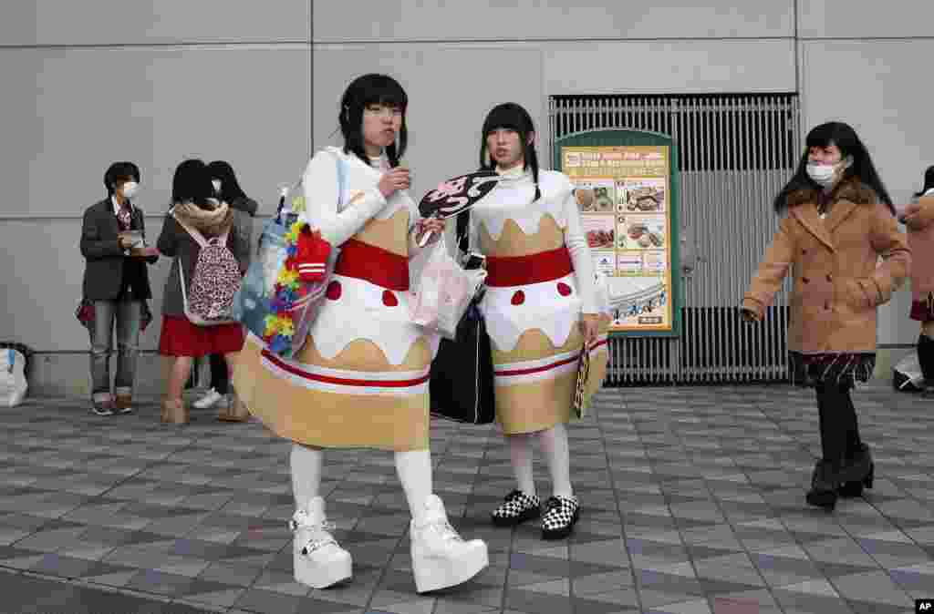 Concertgoers wearing cake-shaped decoration wait outside Tokyo Dome before the concert of a Japanese pop idol group in Tokyo.