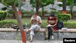 FILE - Indian students study inside the Delhi University campus in New Delhi.
