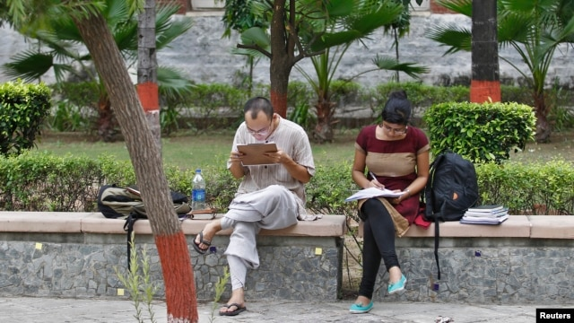 FILE - Indian students study inside the Delhi University campus in New Delhi.