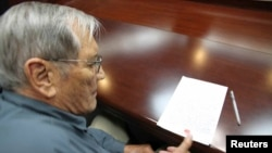 Meril Njumen stavlja otisak prsta na papir u sudnici u Pjongjangu