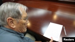 Foto yang dirilis oleh Kantor Berita Resmi Korea Utara (KCNA), menunjukkan Merrill E. Newman, warga AS menorehkan cap jempolnya di sebuah kertas sesaat setelah ditangkap di Korea Utara (30/11).