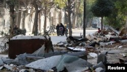 Civilians walk past debris from damaged buildings in the rebel held area of Old Aleppo, Syria, Nov. 14, 2016.