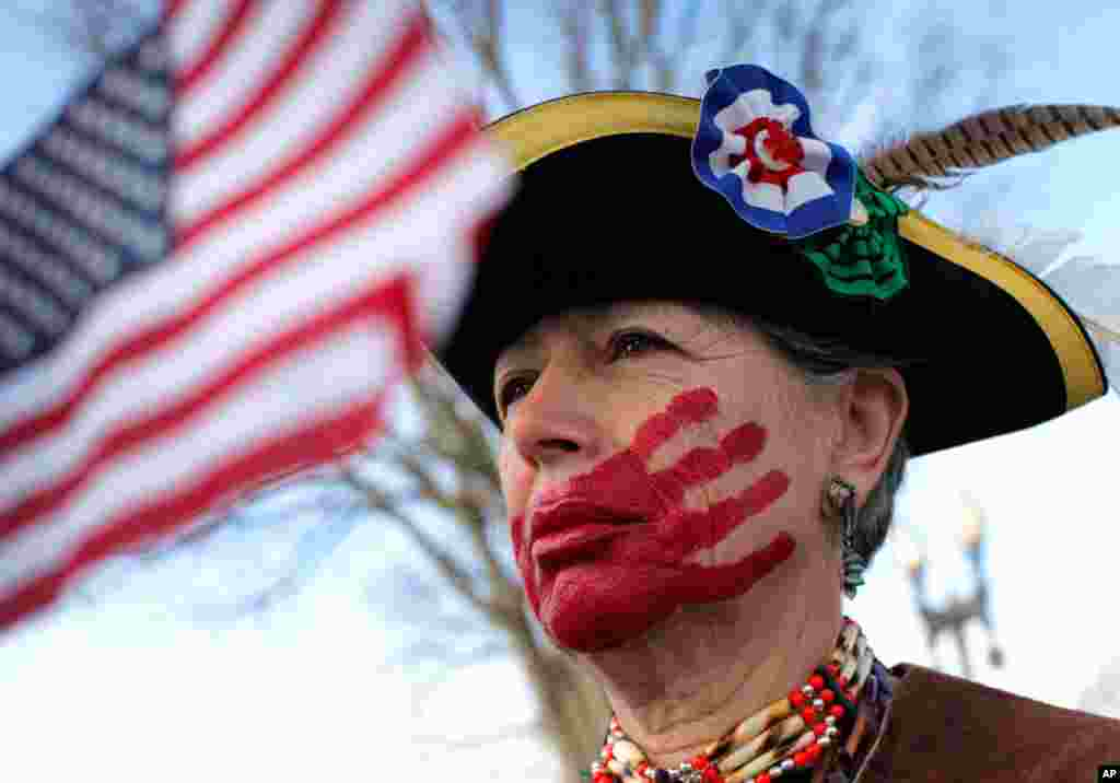 Susan Clark of Santa Monica, Calif., who opposes health care reform, stands with a red hand painted over her mouth to represent what she said is socialism taking away her choices and rights, in front of the Supreme Court, March 28, 2012. (AP)