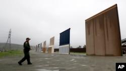 FILE - A Border Patrol agent walks towards prototypes for a border wall in San Diego, California, Feb. 5, 2019.