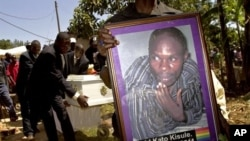 A member of the Ugandan gay community carries a picture of murdered gay activist David Kato during his funeral near Mataba, January 28, 2011. Although the police claims it was most likely a petty crime, targeting Kato's money, many members of the gay and