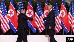 지난 6월 12일 싱가포르에서 열린 첫 미-북 정상회담에서 도널드 트럼프 미국 대통령과 김정은 북한 국무위원장이 악수를 하기 위해 서로에게 손을 내밀고 있다.