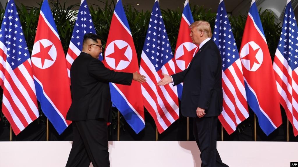 Tư liệu: TT Mỹ Donald Trump và Lãnh tụ Kim Jong Un của Triều Tiên tiến tới bắt tay nhau vào lúc khai mạc hội nghị thượng đỉnh lịch sử ở Singapore vào ngày 12/6/2018. AFP PHOTO / SAUL LOEB