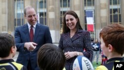 FILE - Britain's Prince William, Duke of Cambridge, and his wife Kate, Duchess of Cambridge meet young French rugby fans at the Trocadero square, in Paris, March 18, 2017.