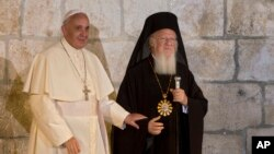 FILE - Pope Francis stands with Ecumenical Patriarch Bartholomew I as they meet outside the Church of the Holy Sepulchre, in Jerusalem's Old City, May 25, 2014.