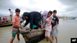 Warga Bangladesh membantu dua perempuan Rohingya turun dari kapal setelah melewati kanal di Shah Porir Deep, di Teknak, Bangladesh, 31 Agustus 2017.