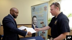 지난달 6일 미국 플로리다주 마이애미에서 열린 참전용사 취업박람회에서 한 남성이 이력서를 제출하고 있다.