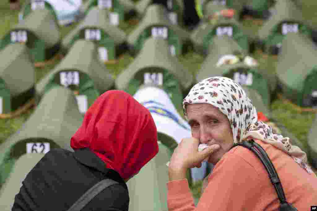 A Bosnian Muslim woman cries near coffins during a memorial ceremony and funeral in Srebrenica. Thousands of people gathered at the Potocari Memorial Center for a memorial ceremony and funeral of 175 victims of Europe's worst massacre since World War II.