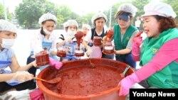 지난 9일 서울 양천구 양천공원에서 열린 전통고추장 담그기 체험행사에 참가한 새마을부녀회 및 다문화, 탈북 여성들이 직접 만든 고추장을 병에 옮겨 담고 있다.