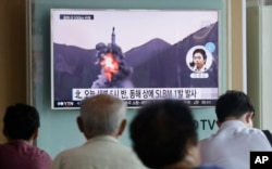 FILE - People watch a TV news program showing a file footage of North Korea's ballistic missile that the North claimed to have launched from underwater, at a Seoul railway station in Seoul, South Korea, Aug. 24, 2016.