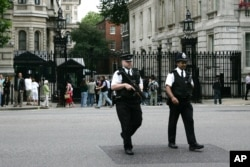 FILE - Armed police officers cross the road outside the security gates at Downing Street in London, Aug 16, 2006.