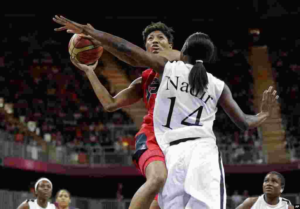 La estadounidense Angel McCoughtry, izquierda, lanza a la canasta sobre Nadir Manuel (14) durante el partido de baloncesto femenino, este lunes, que ganó Estados Unidos, por 90 a 38.