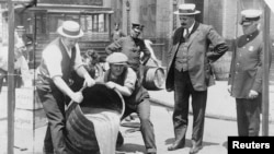 Agents pour liquor into a sewer following a raid during the height of prohibition in an undated photo held by the Library of Congress.