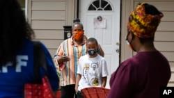 n this Friday, June 5, 2020 photo, Titilaya Thompson and her son Nehemiah talk with Dr. Tayarisha Batchelor, right, and Community School Director for The Village for Families and Children Trisila Tirado, left, in Hartford, Conn. (AP Photo/Jessica Hill)