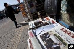 一名北京市民2月16日走过街头报摊,报纸头版刊登中国副主席习近平与奥巴马总统在白宫会晤的照片
