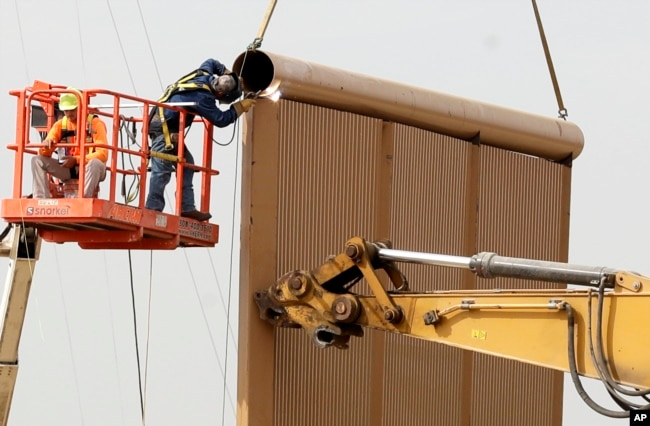 FILE - Crews work on a border wall prototype near the border with Tijuana, Mexico, Oct. 19, 2017, in San Diego, Califiornia.