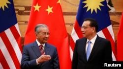 马来西亚总理马哈蒂尔(左)与中国总理李克强在北京人大会堂的签约仪式上。(2018年8月20日)