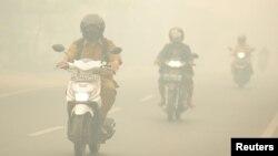 Warga mengendarai motor di tengah kabut asap kebakaran hutan yang menyelimuti Kota Palangkaraya, Kalimantan Tengah, 27 Oktober 2015. (Foto: Antara via Reuters)