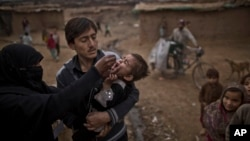 In this file photo, a Pakistani health worker, left gives a polio vaccine to a child, on the outskirts of Islamabad, Pakistan, Wednesday, Jan. 22, 2014. (AP Photo/Muhammed Muheisen)