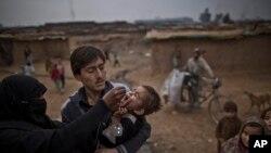 پاکستان کے قبائلی علاقے میں صحت عامہ کی کارکن ایک بچے کو پولیو کے قطرے پلا رہی ہے۔ فائل فوٹو