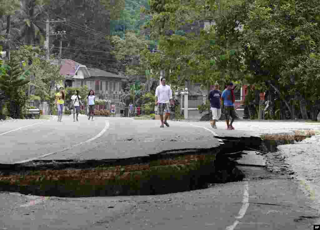 Residents walk on a damaged highway at Loboc township, Bohol province in central Philippines, Oct. 16, 2013.