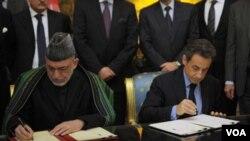 Presiden Perancis Nicolas Sarkozy (kanan) dan tamunya, Presiden Afghanistan Hamid Karzai menandatangani kesepakatan kerjasama dan persahabatan Perancis-Afghanistan setelah pembicaraan di istana Elysee, Paris (27/1).