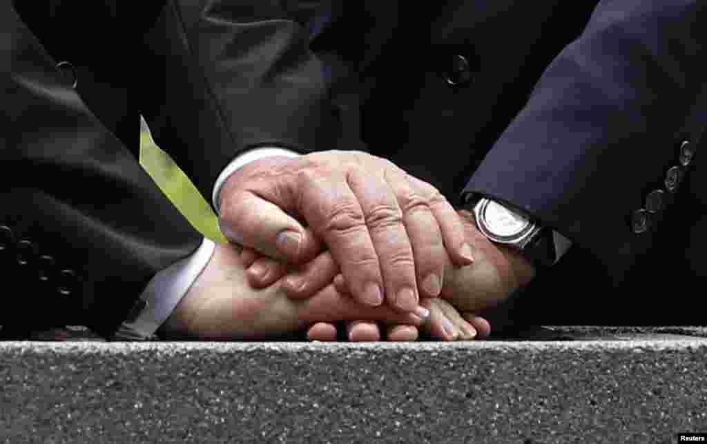The hands of French President Francois Hollande and German President Joachim Gauck are seen during a stone-laying ceremony to mark the 100th anniversary of the100th anniversary of World War I, at the National Monument of Hartmannswillerkopf, in Wattwiller, eastern France, August 3, 2014.
