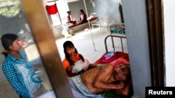 A malaria patient is comforted in the only hospital in Pailin, western Cambodia, file photo.