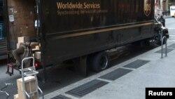 Водитель-экспедитор глобальной компании по доставке грузов UPS выгружает в Манхэттене посылки из грузовика (архивное фото)