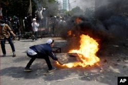 Protesters try to put out fire from a burning tyre in Jakarta, Indonesia, Wednesday, May 22, 2019.