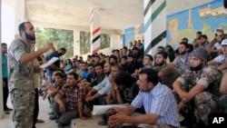 """叙利亚反政府武装""""统一旅""""总指挥官阿卜杜勒-卡迪尔•萨利赫在阿勒颇对手下战士做战前讲话。(2013年8月13日资料照)"""