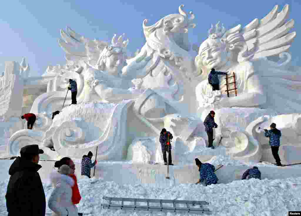 People work on a snow sculpture at the International Snow Sculpture Art Expo in Harbin, Heilongjiang province, China.