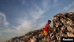 A boy looks for recyclable waste at a rubbish dump outside Yangon January 7, 2016. REUTERS/Soe Zeya Tun - RTX21FSN